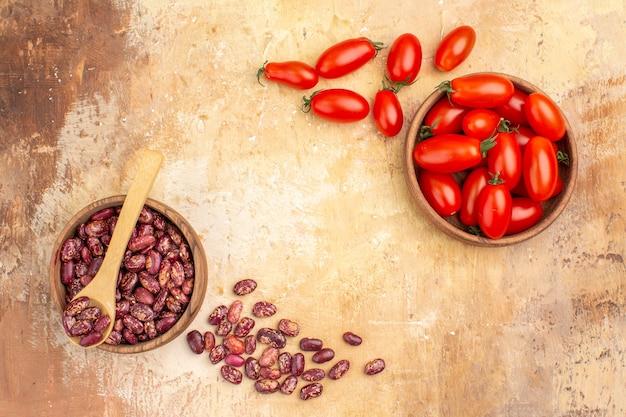 Vista dall'alto dello sfondo della cena con fagioli all'interno e all'esterno della pentola marrone con cucchiaio e pomodori su sfondo di colore misto