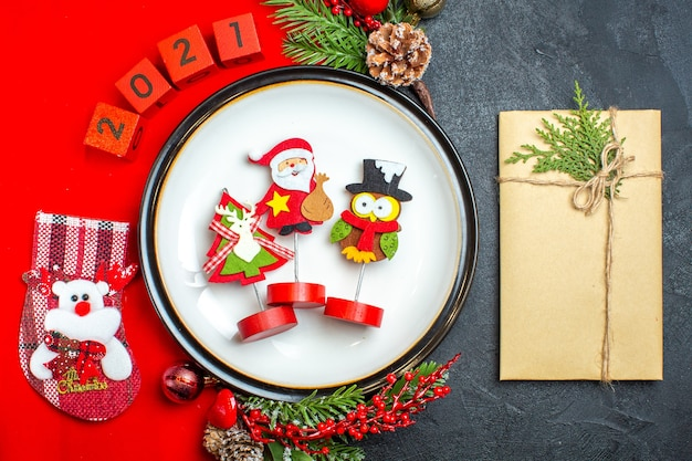 Overhead view of dinner plate decoration accessories fir branches and numbers christmas sock on a red napkin next to gift on a black table