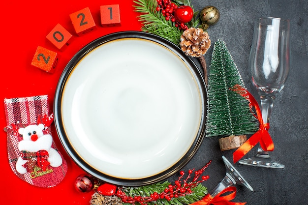 Overhead view of dinner plates decoration accessories fir branches xsmas sock numbers on a red napkin and christmas tree glass goblet on dark background