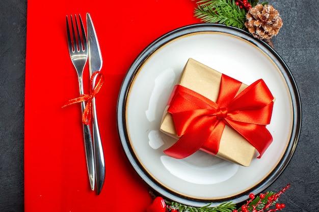 Vista dall'alto di piatti piani con regalo su di esso e set di posate con rami di abete accessorio decorativo cono di conifera su un tovagliolo rosso