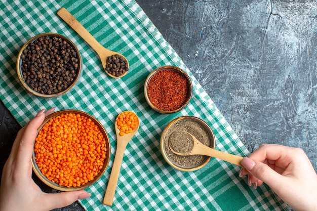 Overhead view of dinner preparation with different spices yellow pea on green stripped towel on dark table
