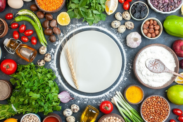 Overhead view of dinner preparation with eggs fresh vegetables green bundles on dark blue