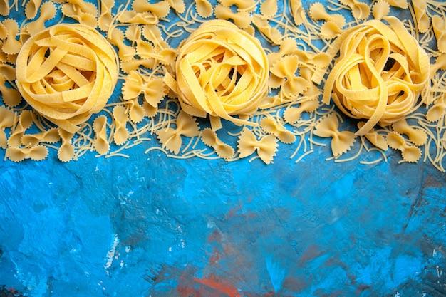 Vista dall'alto della preparazione della cena con spaghetti di pasta allineati in fila su sfondo blu