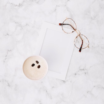 An overhead view of disposable coffee cup; empty frame and eyeglasses on marble textured background
