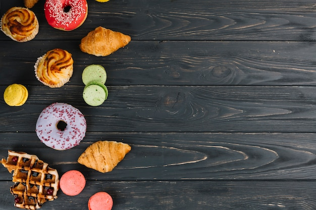 An overhead view of donut; macaroons; croissants; cupcake and waffles on wooden backdrop