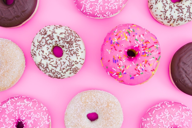 An overhead view of donuts on pink backdrop