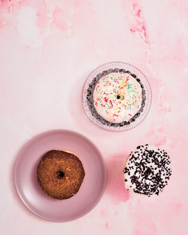 An overhead view of donuts on pink textured background