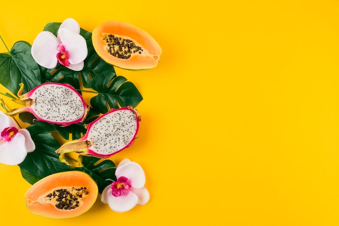 An overhead view of dragon fruits; halved papaya with leaves and orchid flower on yellow backdrop