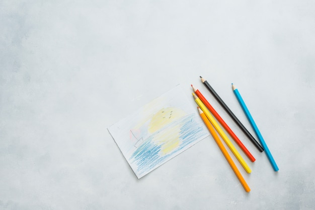 Overhead view of drawn paper and color pencils on white background