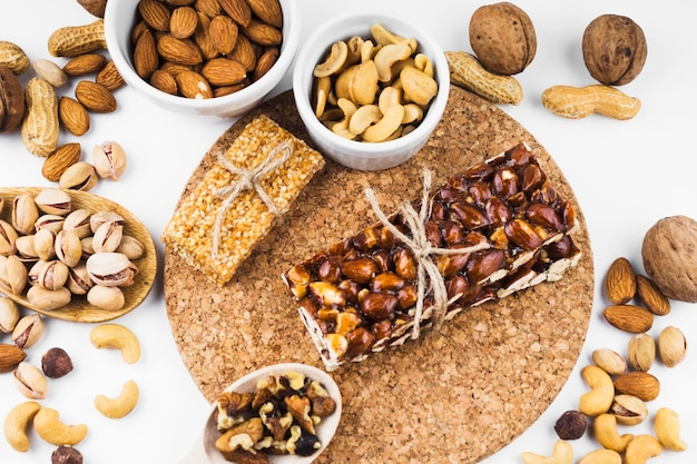 An overhead view of dried fruits and energy bar on white backdrop