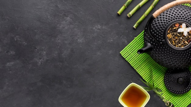 Overhead view of dried herb and bamboo stick with teapot on black backdrop