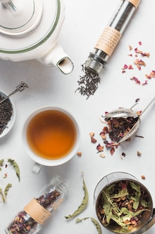 An overhead view of dried herbs with cup of tea and teapot on white background