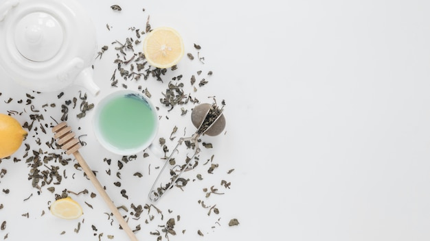 An overhead view of dry tea leaves; tea strainer; lemon; green tea; honey dipper and teapot on white backdrop