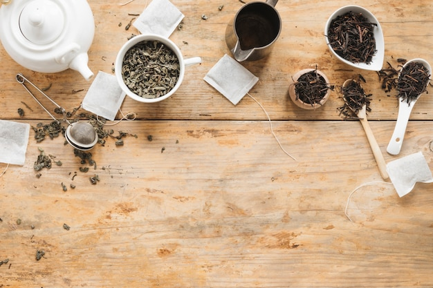 Overhead view of dry tea leaves; teapot; tea strainer; teabag and spoon on wooden table