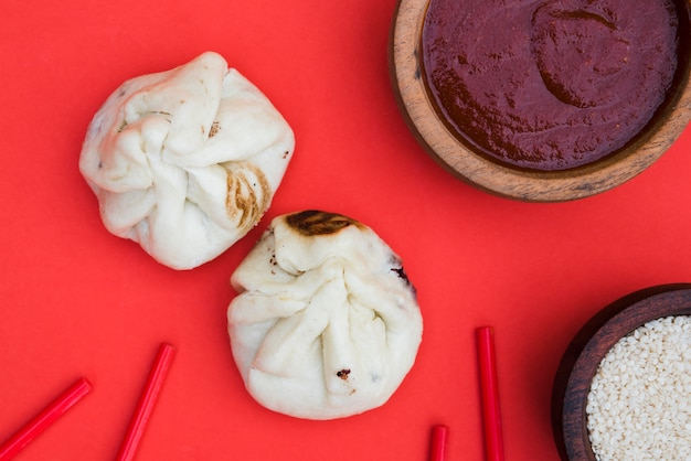 An overhead view of dumplings; chopsticks; sesame seeds and sauces on red backdrop