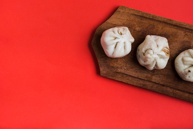 An overhead view of dumplings on wooden tray against red backdrop