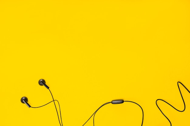 An overhead view of earphone on yellow background with space for text