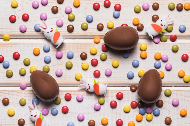 An overhead view of easter eggs and bunnies over the colorful gem candies on wooden desk