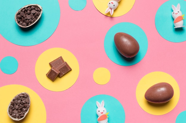 An overhead view of easter eggs; rabbit and choco chips on round frame over the pink background