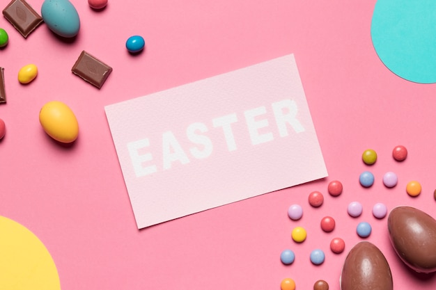 An overhead view of easter word with chocolate easter eggs and gem candies on pink background