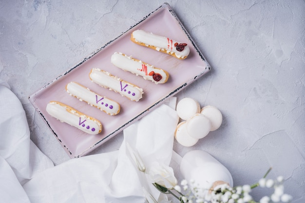 An overhead view of eclair tray with macaroons on textured backdrop