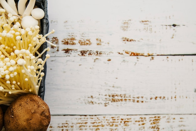 Overhead view of edible mushrooms on white plank