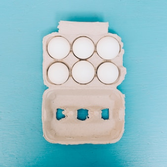An overhead view of eggs in the carton on blue background