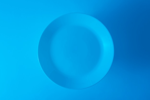 An overhead view of empty blue plate against blue background
