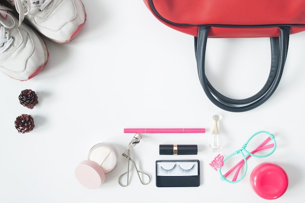 Overhead view of essential beauty items, top view of red hand bag, fashion eyeglasses, cosmetics and sneakers, top view isolated on white background