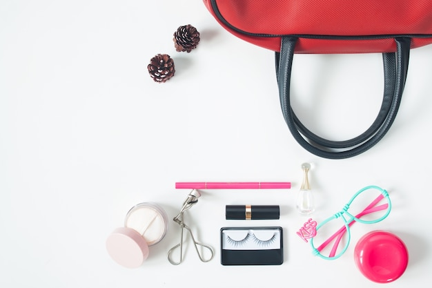 Overhead view of essential beauty items, top view of red hand bag, fashion eyeglasses and cosmetics, top view isolated on white background