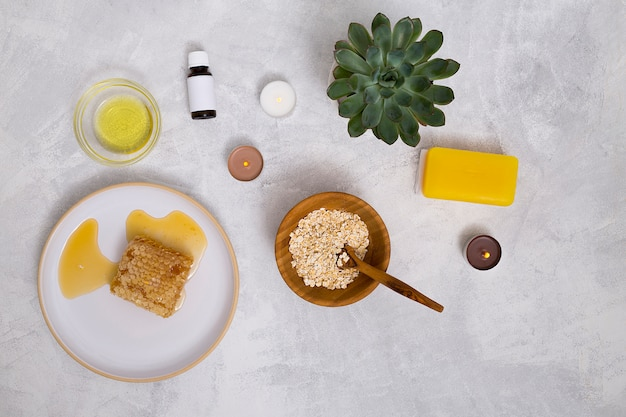 An overhead view of essential oil bottles; oats; cactus plant; yellow soap and honeycomb on concrete background