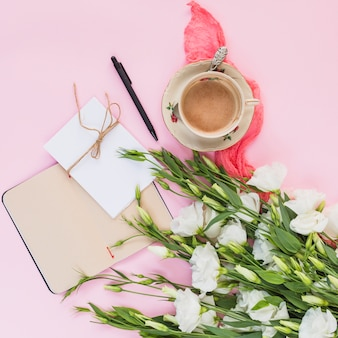 An overhead view of eustoma flowers with diary; card; pen and coffee cup on pink background