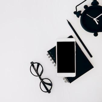 Una vista dall'alto degli occhiali; cellulare; diario; matita e sveglia su sfondo bianco