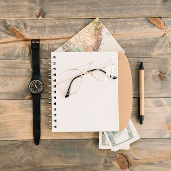 An overhead view of eyeglasses on spiral notepad; currency; map; wristwatch and pen on wooden plank background