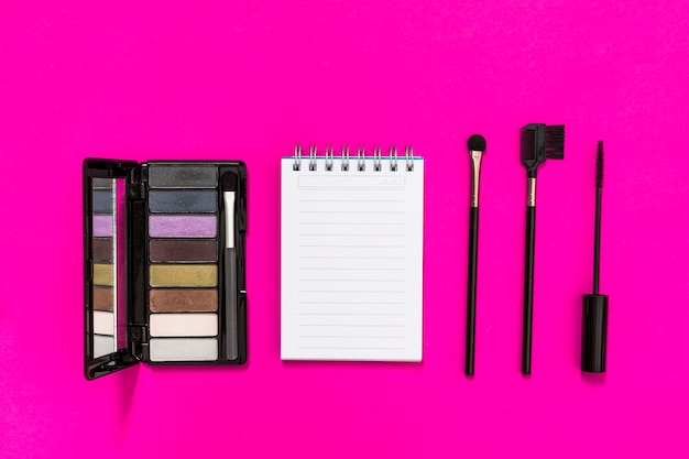 An overhead view of eyeshadow palette; spiral notepad and makeup brushes on pink background
