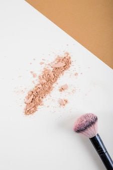 Overhead view of face powder and brush on dual colored background