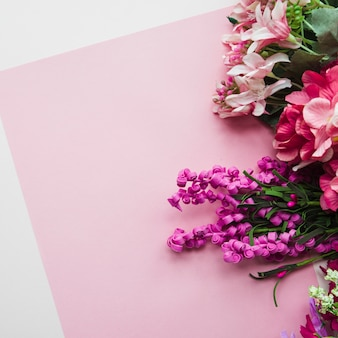 An overhead view of fake flowers on pink backdrop