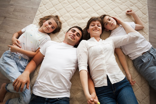 Overhead view of family lying on carpet at home