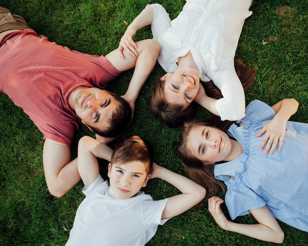 Overhead view of family lying on grass and looking at camera