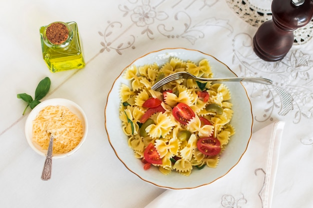 An overhead view of farfalle pasta with cheese and olive on tablecloth