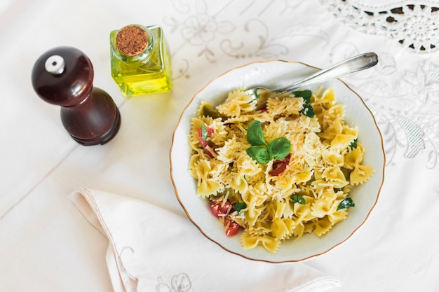 An overhead view of farfalle pasta with cheese; tomatoes and basil leaf in plate