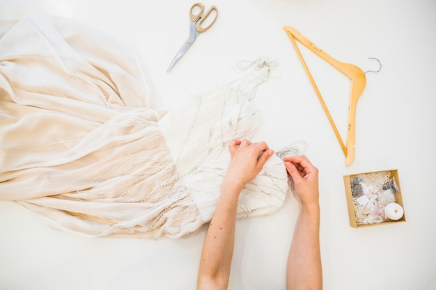 Overhead view of fashion designer's hand sewing dress
