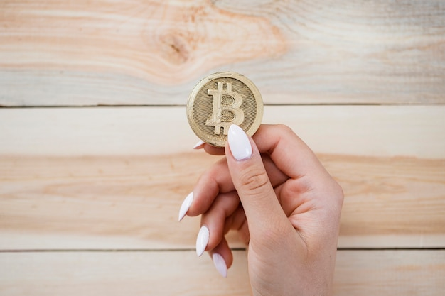 An overhead view of female's hand holding bitcoins against wooden background