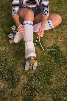 An overhead view of a female skater tying the roller skate lace sitting on green grass
