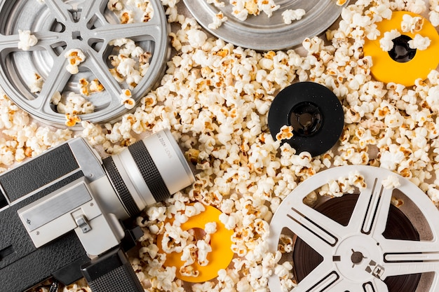 An overhead view of film reel; vintage camcorder; film reels on popcorn