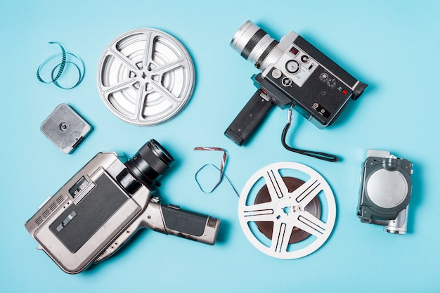 An overhead view of film strips; film reel and various type of camcorder on blue background
