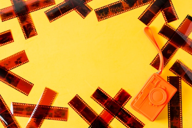An overhead view of film strips with orange purse on yellow background