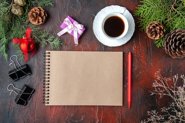 Overhead view of fir branches a cup of black tea decoration accessories and gift next to notebook with pen on dark background