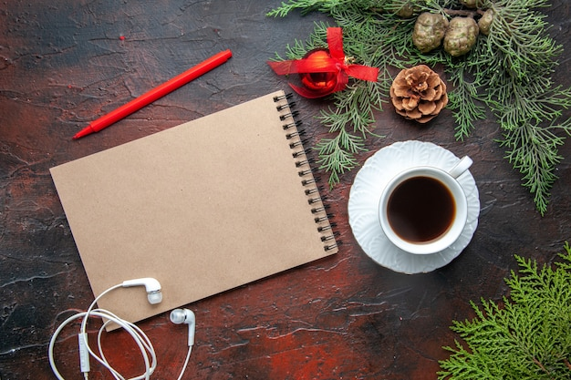 Overhead view of fir branches a cup of black tea decoration accessories white headphone and gift next to notebook with pen on dark background