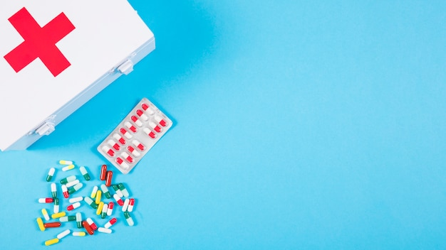 Overhead view of first aid kit with colorful capsules on blue background